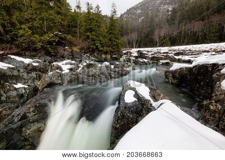 Nature view on the snow covered valley with the river flowing in between the rocks. Picture taken near Tofino Vancouver Island British Columbia Canada.