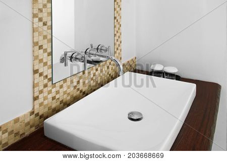 White washbasin and shiny faucet in clean restroom.