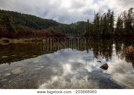 Beautiful nature landscape view of a reflection in the water. Picture taken at Kennedy Lake near Tofino Vancouver Island British Columbia Canada.