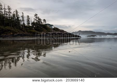 View on the Pacific Ocean Coast during a cloudy winter sunset. Picture taken in Chesterman Beach Tofino BC Canada.
