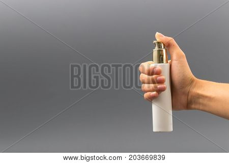 Mini Bottle Sprayer On Gray Background In Hand