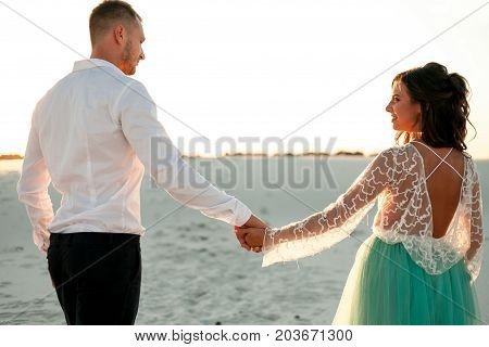 Bride and groom go on sand in desert hold hands and look at each other. They go on background of white sand. Back view. Close up.