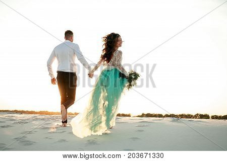 Bride and groom hold hands run on white sand in desert and bride looks back. Back view.