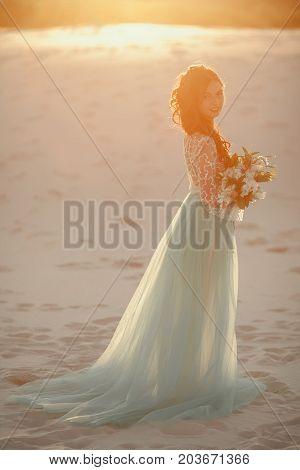 Bride in long wedding dress with bouquet stands on sand in desert. Backlight and pastel colors.