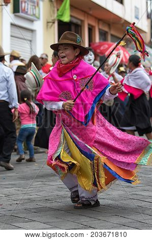 June 17 2017 Pujili Ecuador: young indigenous boy in bright color traditional clothing at Corpus Christi parade dancing in the street