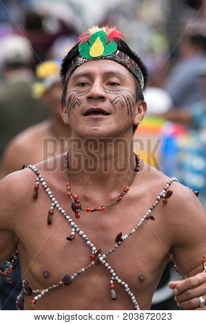 June 17 2017 Pujili Ecuador: bare chested indigenous man from the Amazon area dancing in the street at Corpus Christi parade