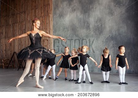 young beautiful blonde female ballerina in black scenic gkfnmt bulky pantyhose and pointe shoes teaches little inattentive girls in black dresses dancing Russian ballet in a dance studio
