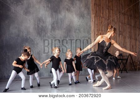 young beautiful blonde female ballerina in black scenic gkfnmt bulky pantyhose and pointe shoes teaches little inattentive girls in black dresses to do bow dancing Russian ballet in a dance studio
