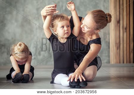 A young beautiful blonde woman ballerina in a black pack white pantyhose and ponts in the style of a black swan teaches a little girl a ballerina to stretch out before the dance in a black studio