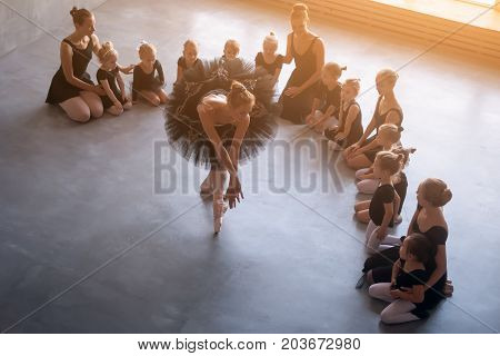 young beautiful blonde woman ballerina in a black dress white pantyhose and pointe dance Russian ballet before the little girls ballerinas in black dresses in a dark dance studio