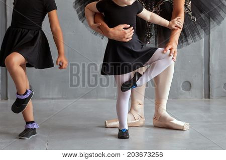 Beautiful dark-haired Russian ballerina in a black festive pack in the style of a black swan and white pantyhose supports and teaches two charming little fair-haired girls to dance the Russian ballet