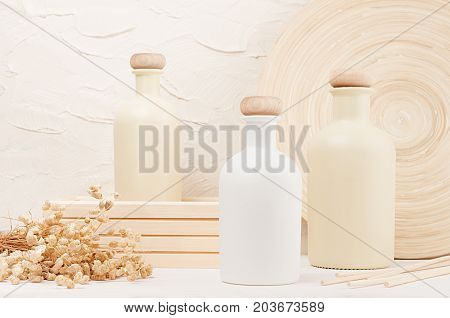 Blank beige cosmetics bottles with spikelets on white wood board mock up. Soft elegant home decor for advertising designers branding identity cover.
