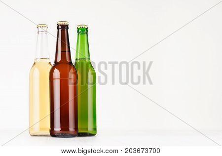 Set brown green transparent longneck beer bottles 500ml mock up. Template for advertising design branding identity on white wood table.