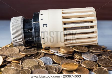Home heat savings or expenses concept. Radiator regulator on a heap of coins.