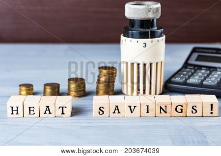 Home heat savings or expenses cost concept. Radiator regulator with coin stacks.