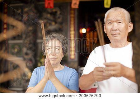 asian senior couple praying buddha with incense stick