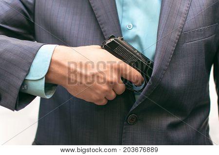 Elegant man in suit pulls out a gun. Smart Killer.