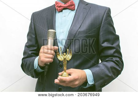 Man in suit with microphone in hand presenting an golden award to someone. The award ceremony. Success. Gratitude concept. Showman.