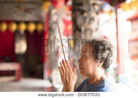 senior woman praying buddha with incense stick at temple