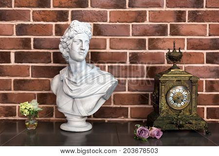White plaster bust sculpture portrait of a young man and old clock on the table, details of luxury interior in classic style