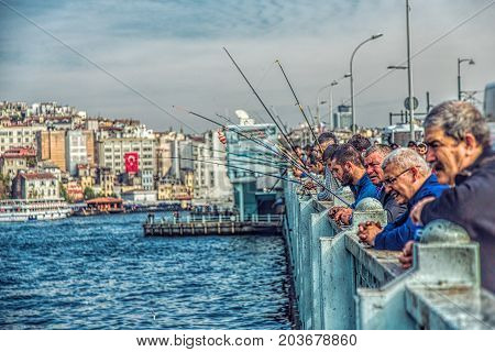 ISTANBUL, TURKEY: Fishermen on Galata Bridge in Istanbul, Turkey. Galata Bridge is one of the famous entertainment place in Istanbul. On October 7, 2014