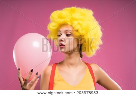 A woman clown in a ladylike wig looks at an inflatable ball. Isolated on a pink background