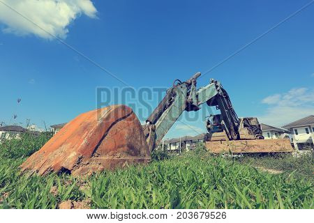 old excavator construction machinery of industry parked on grass field