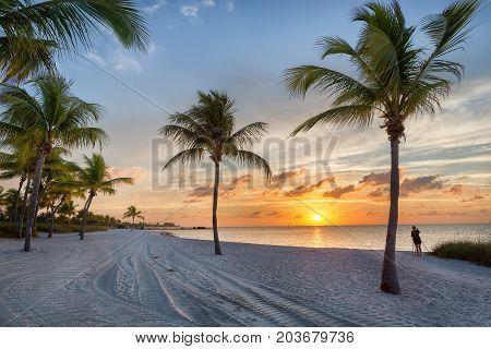 Photographer at sunrise on the Smathers beach - Key West, Florida