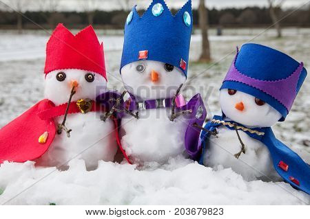 Three cute king snowmen dressed with crowns and capes looking very regal. Snow fall background in a rural winter scene