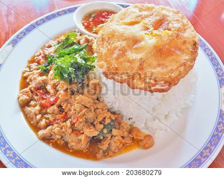 Steamed rice topped with Thai basil pork stir-fry (PAD GA PRAO) and fried egg served with chili fish source, famous Street food in Thailand. Traditional Thai cuisine.