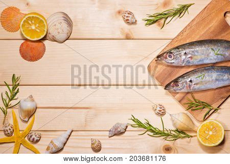 Fish Dish Cooking With Various Ingredients. Fresh Raw Fish Decorated With Lemon Slices And Herbs On