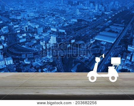 Motor bike icon on wooden table over modern city tower street and expressway Business delivery service concept