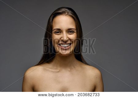 Attractive smiling woman with bare shoulders and long brown hair posing over a dark grey studio background facing the camera