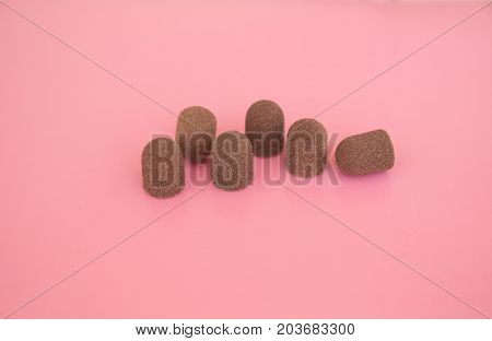 Grinding Drill Caps. Brown Color Caps On The Pink Background