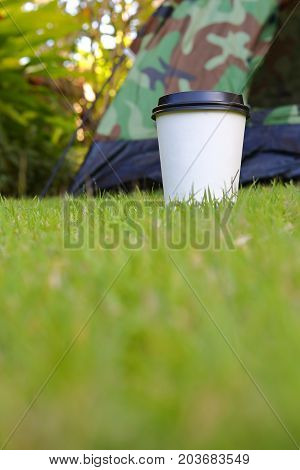 Hot Coffee Drink, White Disposable Cup On Green Grass Lawn Campsite