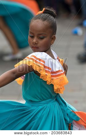 June 17 2017 Pujili Ecuador: young indigenous girl in bright colour traditional clothing at Corpus Christi parade dancing in the street