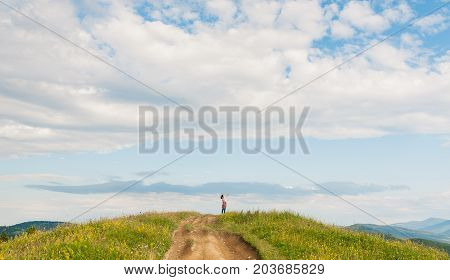 Curly young woman look for to talk to the phone standing on beautiful landscape of mountain in summer. Modern people using portable mobile devices everywhere they go. Amazing blue sky background
