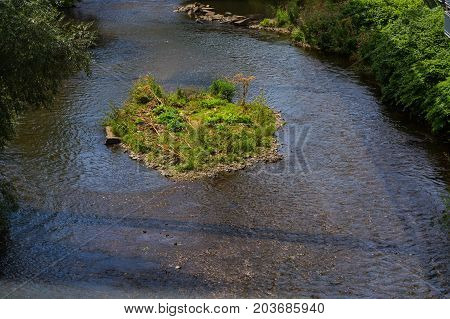 The river Wupper in Wuppertal Germany with a small island in the river bed. Photographed from the suspension railway.