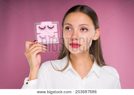 A beautiful girl holds false eyelashes in her hands, looks somewhere. Isolated on a pink background