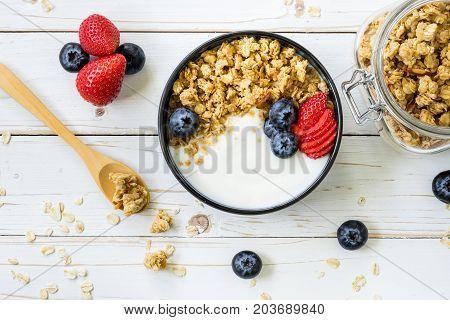 bowl of granola with yogurt fresh berries strawberry on wood table.