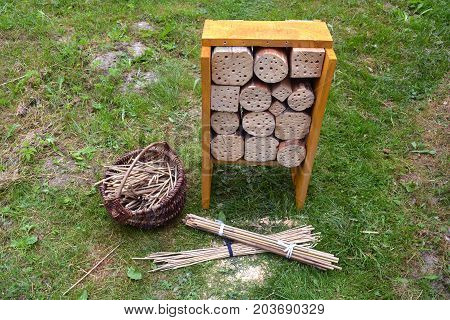 New Insect hotel and reeds in basket in garden on grass