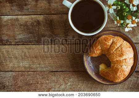 Homemade croissant served with black coffee or americano. Delicious breakfast with fresh croissant and coffee. Croissant and black coffee and chamomile with copy space in top view or flat lay style. Croissant and coffee for coffee break.
