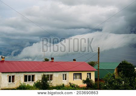 Thunderclouds over the house in the village