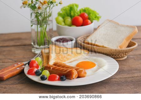 Homemade breakfast with sunny side up fried egg toast sausage fruits vegetable strawberry jam in side view with copy space.Delicious homemade american breakfast concept for background or wallpaper. American breakfast served on wood table.