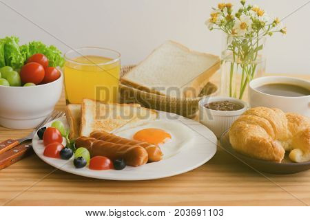 Homemade breakfast with sunny side up fried egg toast sausage fruits vegetable strawberry jam and orange juice in side view with copy space. Delicious homemade american breakfast concept for background. American breakfast served on table.