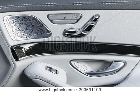 Door handle with Power seat control buttons of a luxury passenger car. White leather interior of the luxury modern car. Modern car interior details