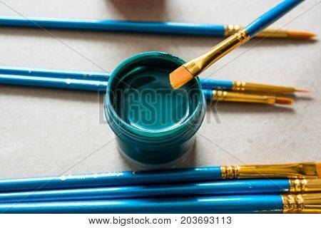 Green plastic jar with paint and brush. Artist's work place