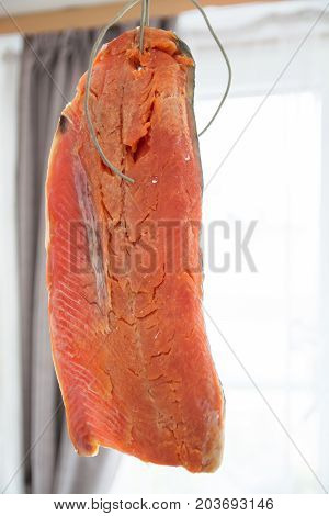 Fillet of fresh red fish hang on rope.The homemade drying of fish.