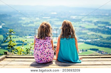 Children - Twin Girls Sitting On Paragliding Ramp After Hiking.