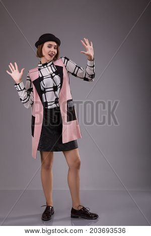 Portrait of extraordinary woman dressed in black hat and plaid shirt staying over gray background. Studio shoot